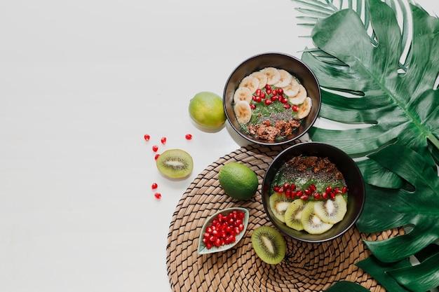 Концепция здорового питания. вид сверху на стол с мисками для смузи. тарелка с киви, мюсли, гранатом, чиа, авокадо. Бесплатные Фотографии