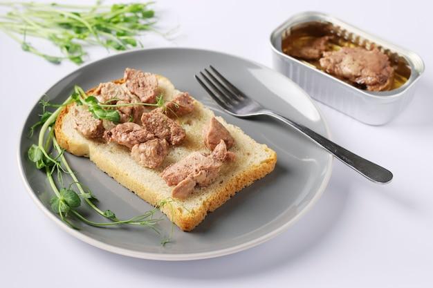 Здоровая еда, бутерброд с печенью трески и гороховых микрогрин на серой тарелке на белом фоне Premium Фотографии