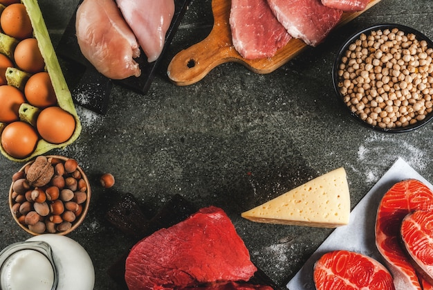 Healthy food . selection of protein sources: beef and pork meat, chicken  filet, salmon fish, egg, beans, nuts, milk. top view copyspace, dark background frame Premium Photo