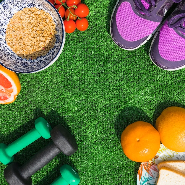 Healthy food with pair of sport shoes and dumbbells on turf Free Photo