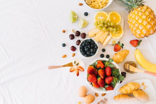 Healthy fresh fruits with egg and croissant on white background Free Photo