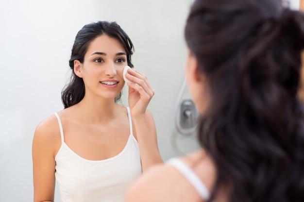 Здоровая свежая девушка удаляет макияж с лица ватным диском Premium Фотографии