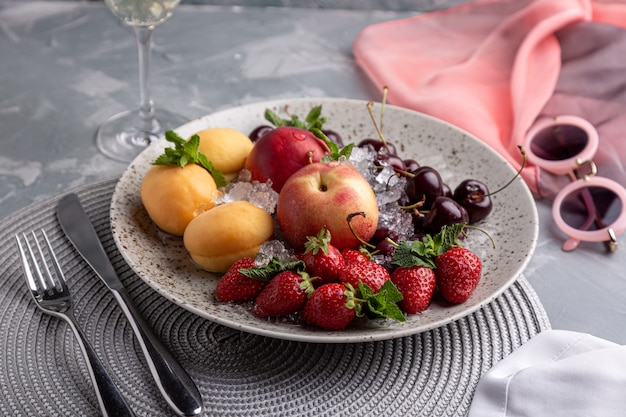 健康的なフルーツの盛り合わせ、イチゴ、リンゴ、桃、アプリコット、暗い灰色の木製テーブル、平面図、クローズアップ、セレクティブフォーカス。 Premium写真