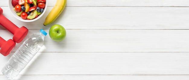 Healthy fruits. fresh fruits salad diet slim fit with dumbbells sport equipment on wooden table background Premium Photo