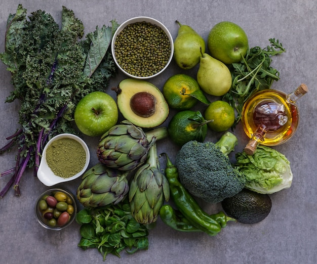 Healthy green food selection for vegetarians: avocado, apples, broccoli, artichokes, tangerines, mung beans, lettuce, olives, rucola, kale, matcha tea, pears Premium Photo