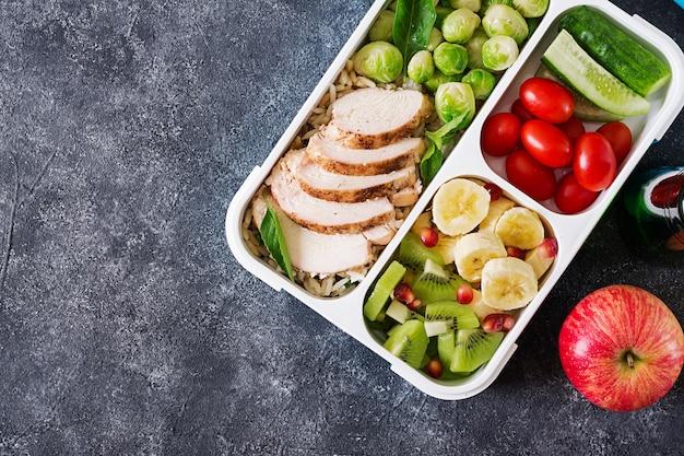 치킨 필렛, 쌀, 브뤼셀 콩나물, 야채와 과일 오버 헤드 샷 건강 한 녹색 식사 준비 컨테이너 복사 공간. 도시락에서 저녁 식사. 평면도. 평평하다 프리미엄 사진