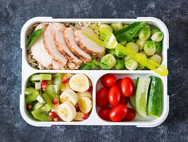 Healthy green meal prep containers with chicken fillet, rice, brussels sprouts, vegetables and fruits Premium Photo