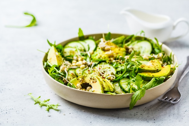 Healthy green salad with avocado, cucumber and arugula in white dish. Premium Photo