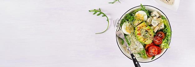 卵、米、トマト、アボカド、ブルーチーズとテーブルの上の健康的な緑のベジタリアンボウルランチ。 無料写真