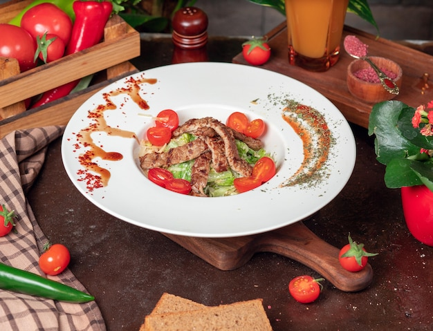 Healthy grilled beef caesar salad with cheese, cherry tomatoes and lettuce Free Photo