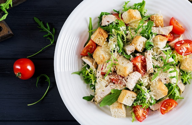 Healthy grilled chicken caesar salad with tomatoes, cheese and croutons. Premium Photo