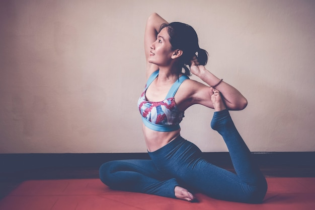 Healthy and happy asian woman practicing yoga, one legged king pigeon pose at home, wellness and fitness lifestyle Premium Photo