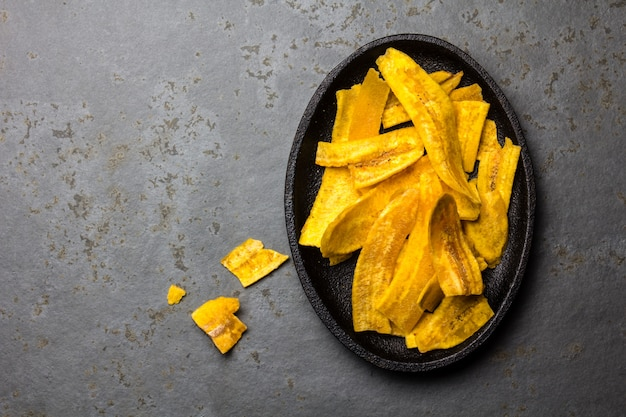 Healthy homemade banana plantain chips on black plate Premium Photo