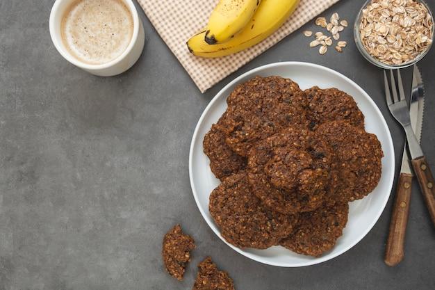 バナナとオーツ麦のフレーク、ドライフルーツ、種子入りのヘルシーな自家製クッキー。 Premium写真