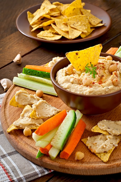 Healthy homemade  hummus with olive oil and pita chips Free Photo