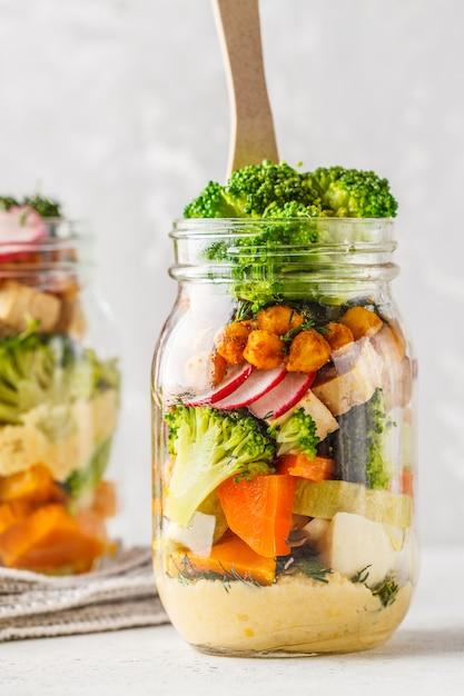 健康的な自家製メイソンジャーサラダ、焼き野菜、フムス、豆腐、ひよこ豆。 Premium写真