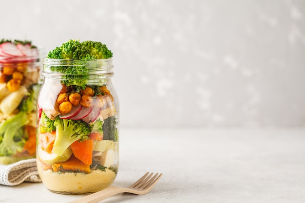 Healthy homemade mason jar salad with baked vegetables, hummus, tofu and chickpeas, copy space. Premium Photo