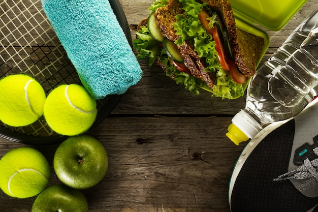 Healthy Life Sport Concept. Sneakers with Tennis Balls, Towel, Apples, Healthy Sandwich and Bottle of Water on Wooden Background. Copy Space. Above. Free Photo
