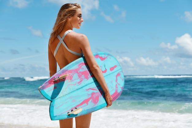 Концепция здорового образа жизни и отдыха. вид сзади беззаботной женщины в купальнике и солнечных очках, задумчиво смотрит на океан, несет доску для серфинга, любит летние виды спорта. женщина на пляже Бесплатные Фотографии