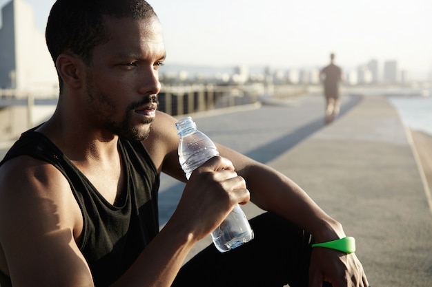 Healthy lifestyle concept. profile portrait of black sportsman with muscular body sitting on pavement in morning sun after training exercises, holding bottle, drinking water, looking into distance Free Photo