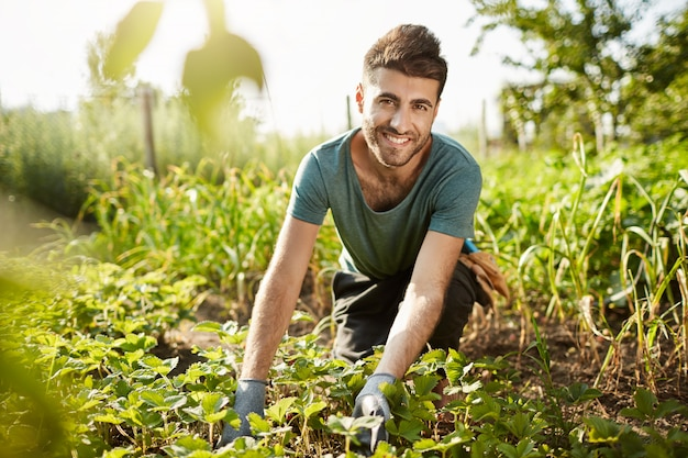 Healthy lifestyle. countryside life. close up outdoors portrait of young attractive bearded caucasian farmer smiling, spending morning in garden near house, picking crop Free Photo