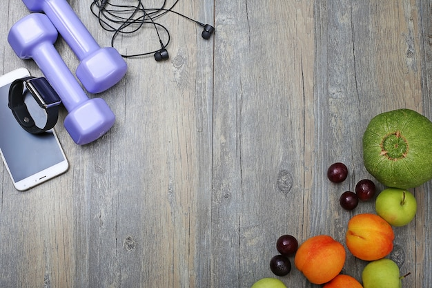 healthy lifestyle dumbbell smart watch and fruit Free Photo