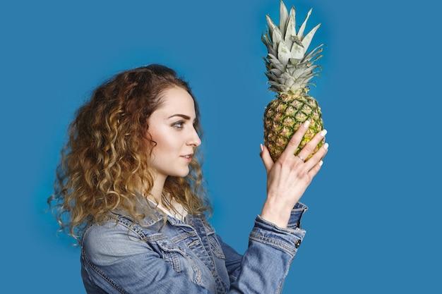 健康的なライフスタイル、果物食主義、夏、ダイエット、食品、栄養の概念。フルーツサラダに熟した甘いパイナップルを選ぶウェーブのかかった髪のスタイリッシュな若い白人女性の横向きの肖像画 無料写真
