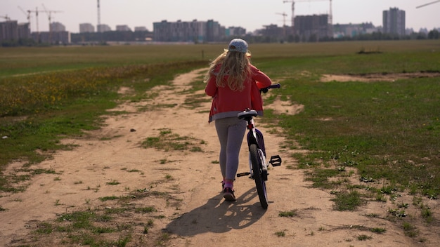 Healthy lifestyle - girl with a bicycle walking on a field near the city Premium Photo