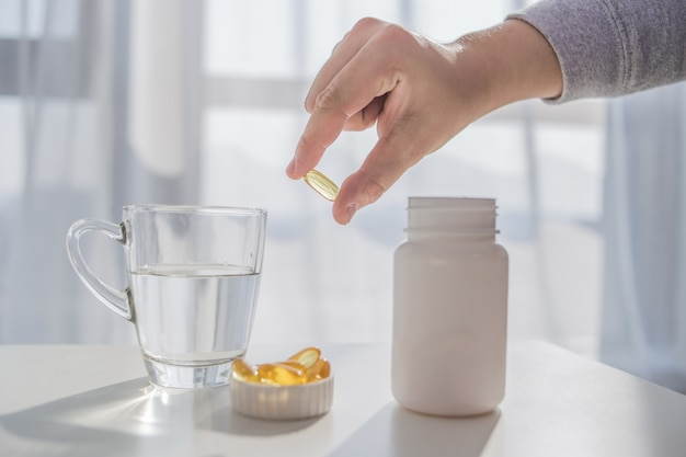 Healthy lifestyle, medicine, nutritional supplements and people concept - close up of male hands holding pills with cod liver oil capsules and water glass Free Photo
