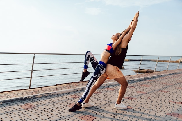 Healthy lifestyle. young woman and man doing sports exercises for body together Free Photo