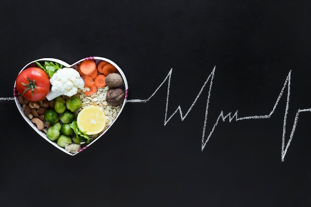 Healthy living concept with vegetables arranged in heartshape as an ecg life line on black background Free Photo