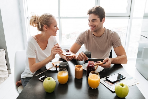 Healthy lovers sitting in kitchen and eating breakfast Free Photo