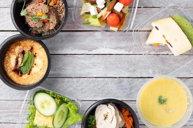 직장에서 건강 한 점심. 음식 상자, 아침 식사 및 점심 식사에서 먹을 준비가 된 식사, 회색 테이블에 칼이 달린 검은 용기에서 식사를하십시오. 프리미엄 사진