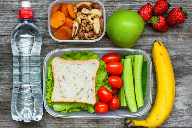 サンドイッチと新鮮な野菜、水のボトル、ナッツ、フルーツのヘルシーなランチボックス Premium写真