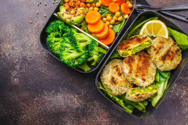 Healthy meal prep containers with green burgers, broccoli, chickpeas and salad. Premium Photo