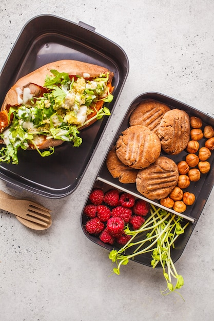 Healthy meal prep containers with quinoa stuffed sweet potatoes, cookies and berries, overhead shot. Premium Photo