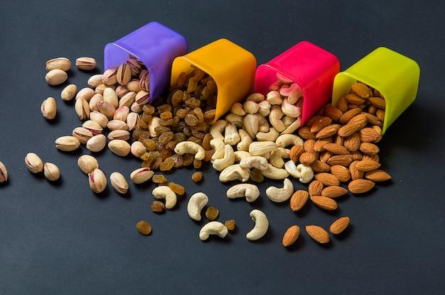 健康的なミックスドライフルーツとナッツの暗い背景。アーモンド、ピスタチオ、カシューナッツ、レーズン Premium写真
