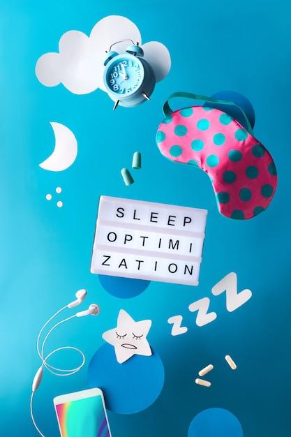 Концепция здорового сна ночью творческий журнал сна или дневник сна. летающие или левитирующие предметы: маска для сна, будильник, смартфон, наушники, затычки для ушей и таблетки. бумажная звезда, zzz, луна, облака. Premium Фотографии