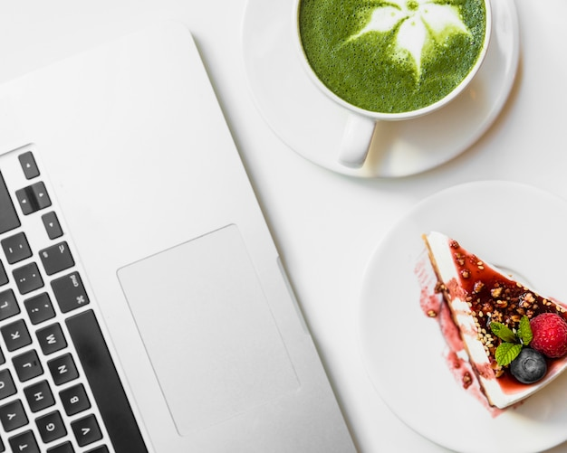 Healthy organic summer dessert; matcha tea cup near the laptop on white desk Free Photo