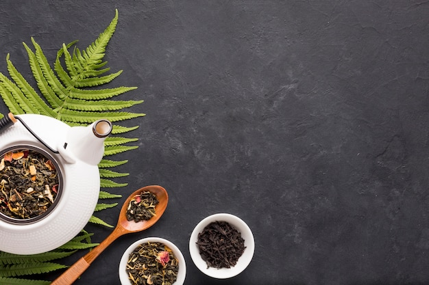 Healthy organic tea with dry herb and fern leaves on black surface Free Photo