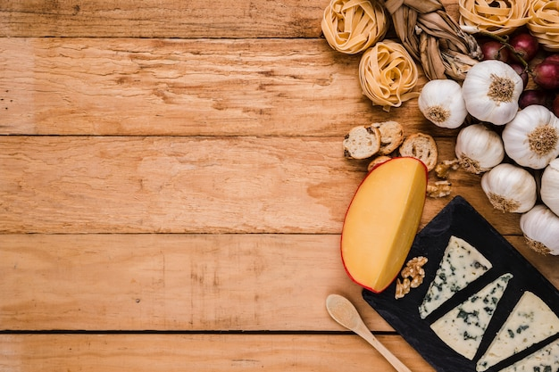 Healthy raw ingredients with fresh cheese over wooden panel with space for text Free Photo