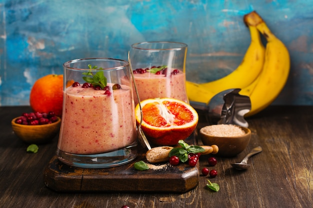 Healthy refreshing pink smoothie with apple, red oranges, cowberry and bran Premium Photo