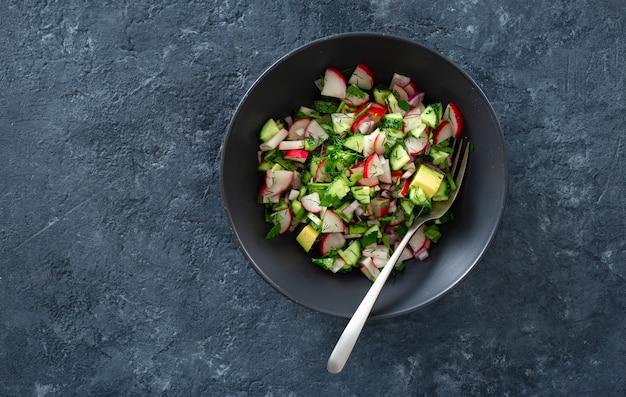 Healthy salad bowl radish cucumber avocado top view Premium Photo