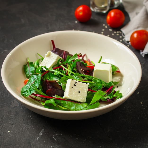 Healthy salad leaves in a white plate and cheese (mix micro greens, juicy snack). food background Premium Photo