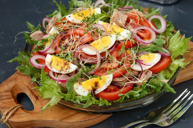 Healthy salad of organic salad with canned tuna, tomatoes, chicken eggs and red onion. Premium Photo
