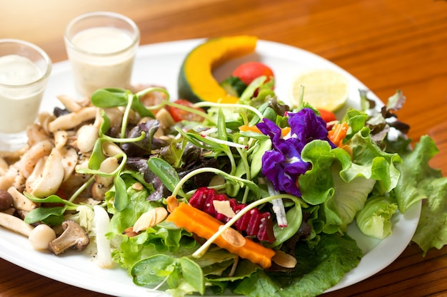 Healthy salad on a plate placed on a wooden table. Premium Photo