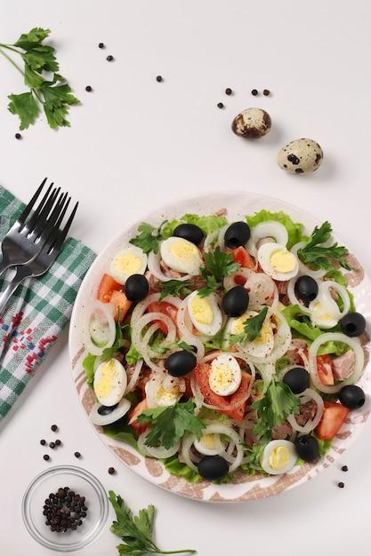缶詰のマグロ、トマト、ウズラの卵、ブラックオリーブ、白ねぎ、白い表面に有機レタスを添えたヘルシーサラダ、上面図、垂直フォーマット Premium写真