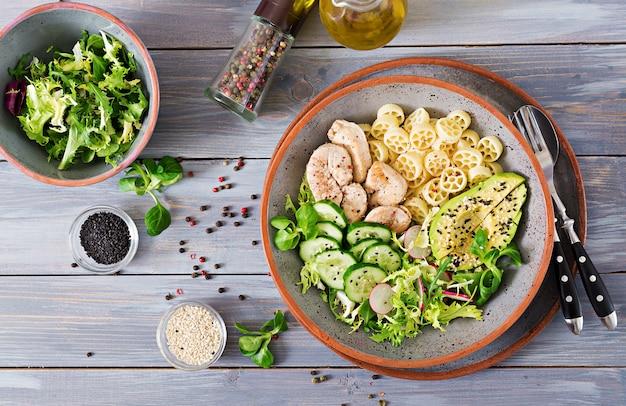 Healthy salad with chicken, avocado, cucumber, lettuce, radish  and pasta on dark Premium Photo