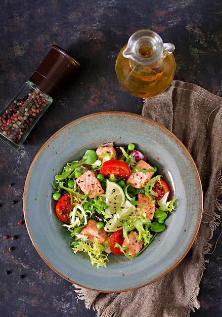 Healthy salad with fish. baked salmon, tomatoes, lime and lettuce. healthy dinner. flat lay. top view Free Photo