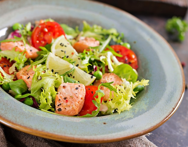 Healthy salad with fish. baked salmon, tomatoes, lime and lettuce. healthy dinner. Free Photo